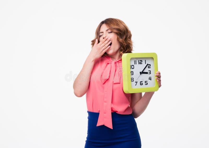 Femme fatiguée tenant l'horloge images stock