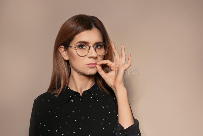 Femme fermant la fermeture éclair sa bouche sur le fond de couleur Utilisant la langue des signes images stock