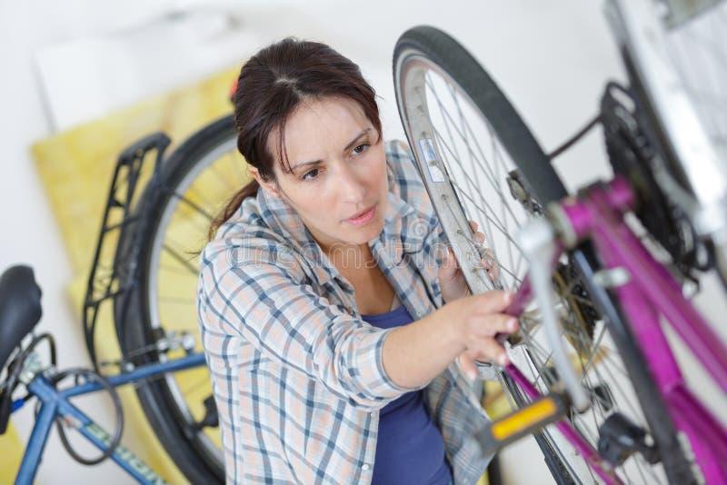Femme fixant le vélo photos libres de droits