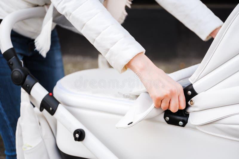 Femme flânant avec le bébé-chariot Fermez-vous des mains femelles ajustent le bébé-chariot d'auvent photo stock