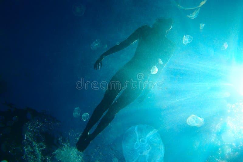 Femme flottant dans l'océan photo libre de droits