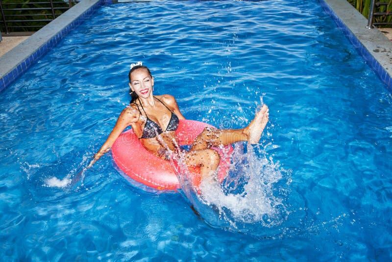 Femme flottant dans la chambre à air dans la piscine et ayant l'amusement images stock