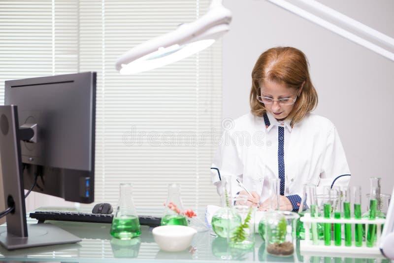 Femme focalisée de Moyen Âge prenant des notes après essai scientifique dans un laboratoire de production image stock