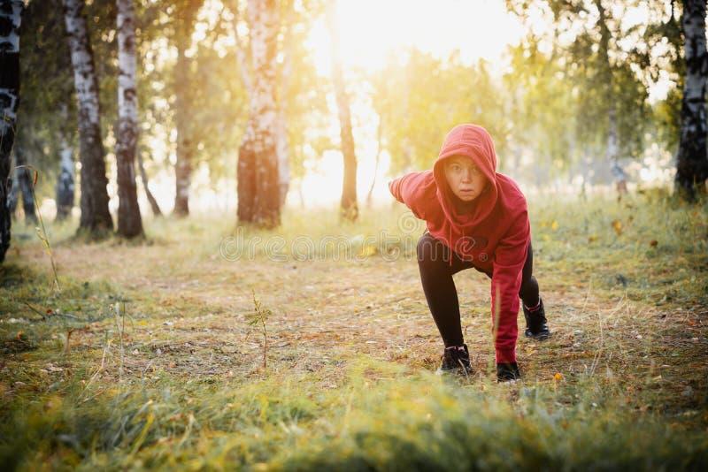 Femme focalisée s'exerçant en parc de ville sports photo libre de droits