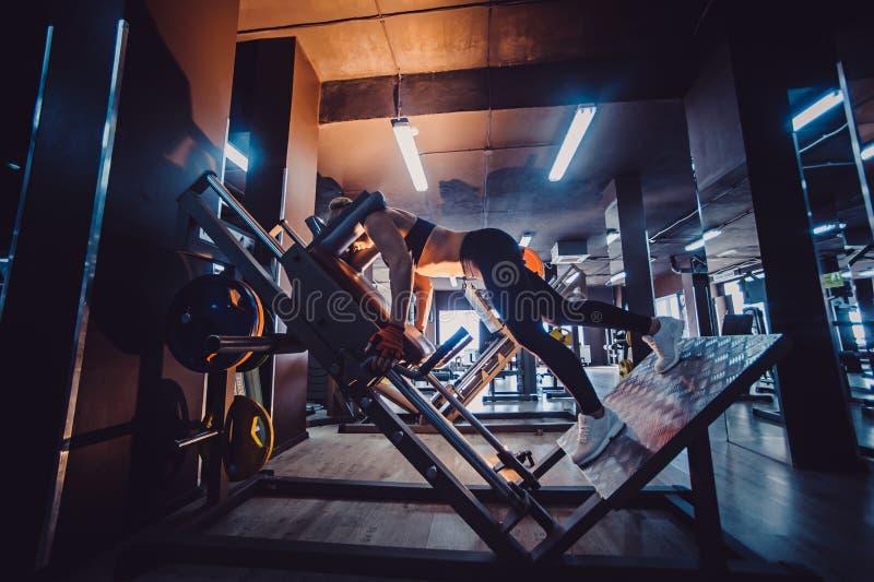 Femme folâtre à l'aide de la machine pour des jambes au gymnase Exercice assez blond dans un simulateur images libres de droits