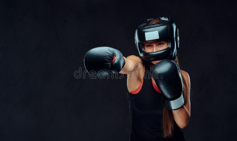 Femme folâtre dans les vêtements de sport portant un casque de protection et les gants de boxe, formation dans le gymnase D'isole image stock
