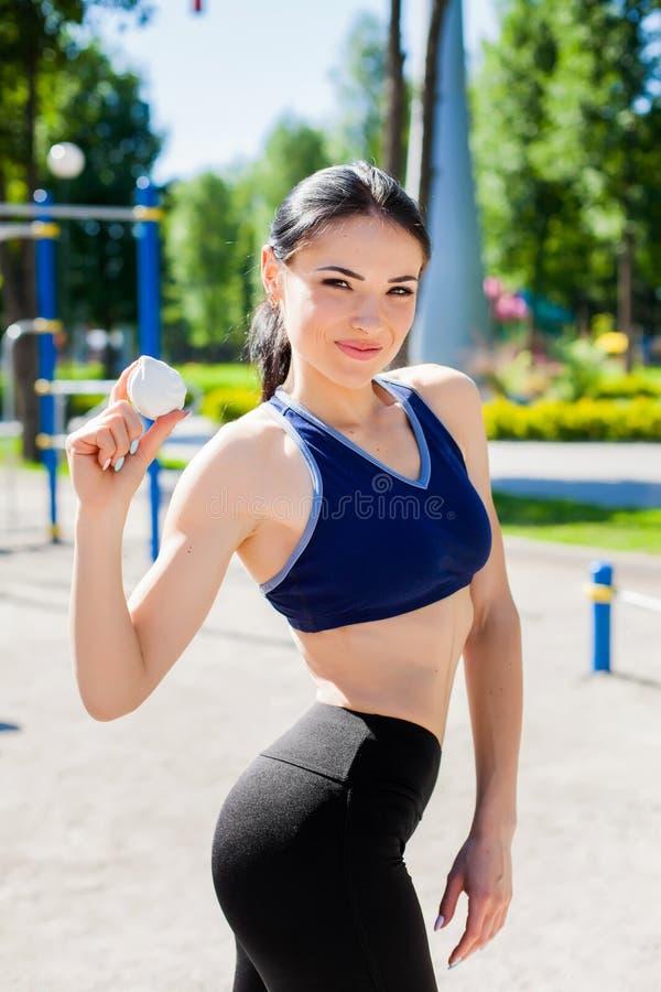 Femme folâtre sur le terrain de jeu de sport avec la guimauve photo stock