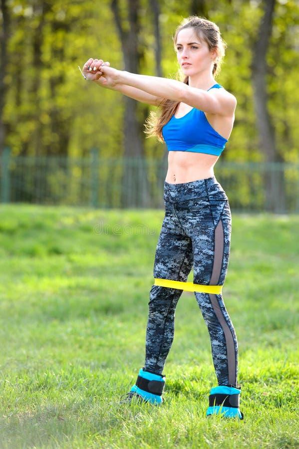 Femme forte dans les vêtements de sport faisant des postures accroupies Photo du travail musculaire de modèle de forme physique images stock