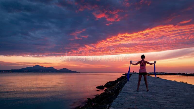 Femme forte de confiance faisant la séance d'entraînement sous le lever de soleil au bord de la mer photos stock
