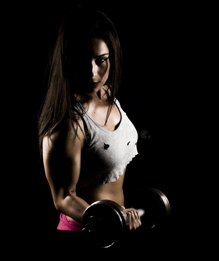 Femme forte de forme physique établissant avec les poids lourds photographie stock libre de droits