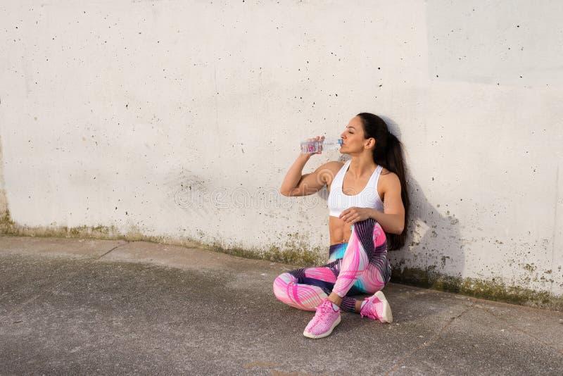 Femme forte de forme physique se reposant pour l'eau potable  photographie stock