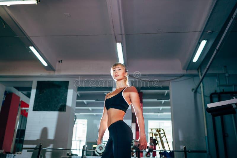Femme forte de forme physique tenant des haltères photos libres de droits