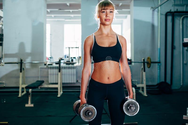 Femme forte de forme physique tenant des haltères photos stock