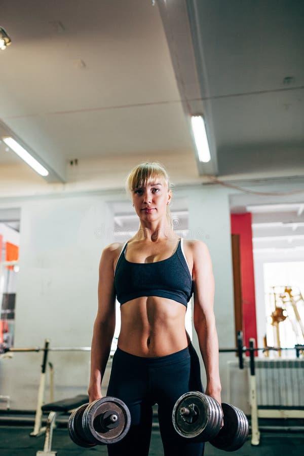 Femme forte de forme physique tenant des haltères photographie stock