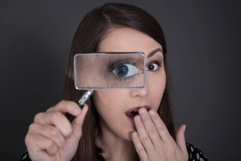 Femme fouineuse et choquée d'affaires dans le noir tenant des glas de agrandissement photographie stock libre de droits