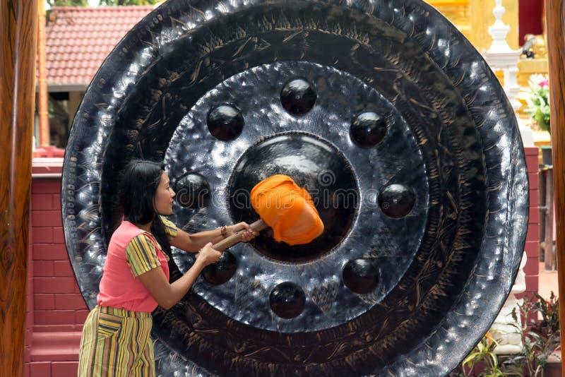 Femme frappant un gong photo stock