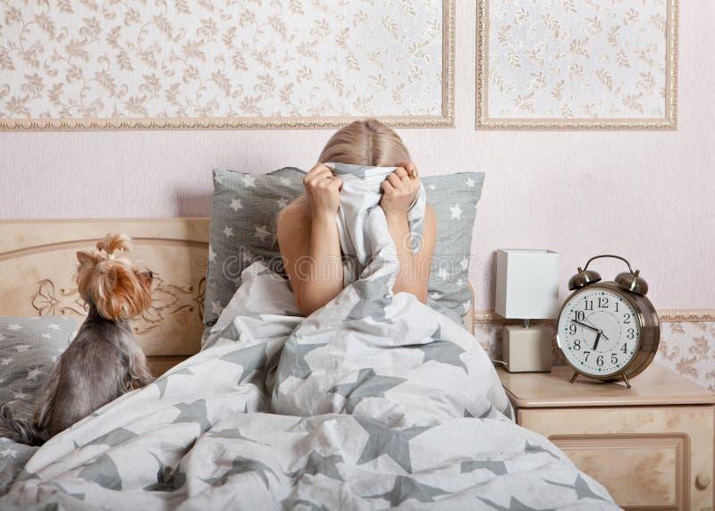 Femme frustrée assise au lit, enterrée dans la couverture images stock