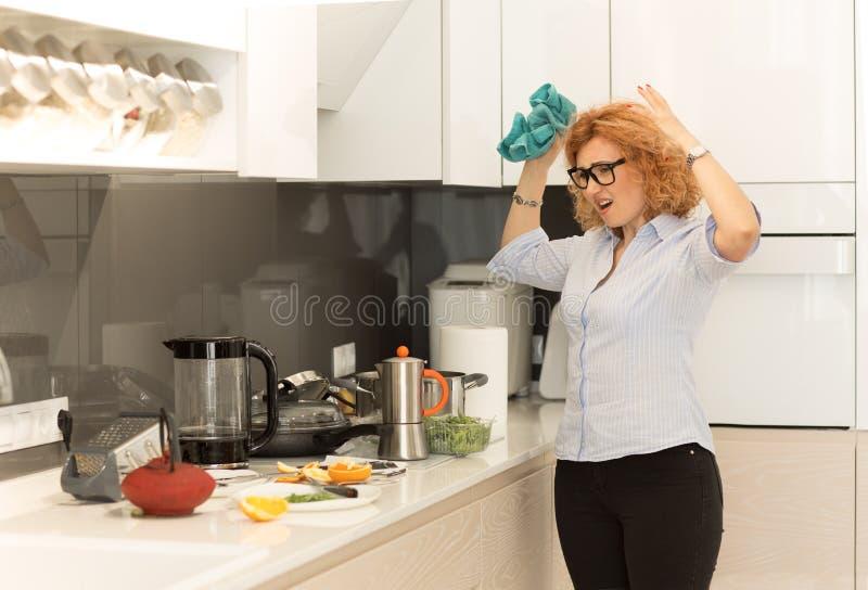 Femme frustrée, les mains dans l'air, frustrée, regardant les assiettes sales dans la cuisine photo stock