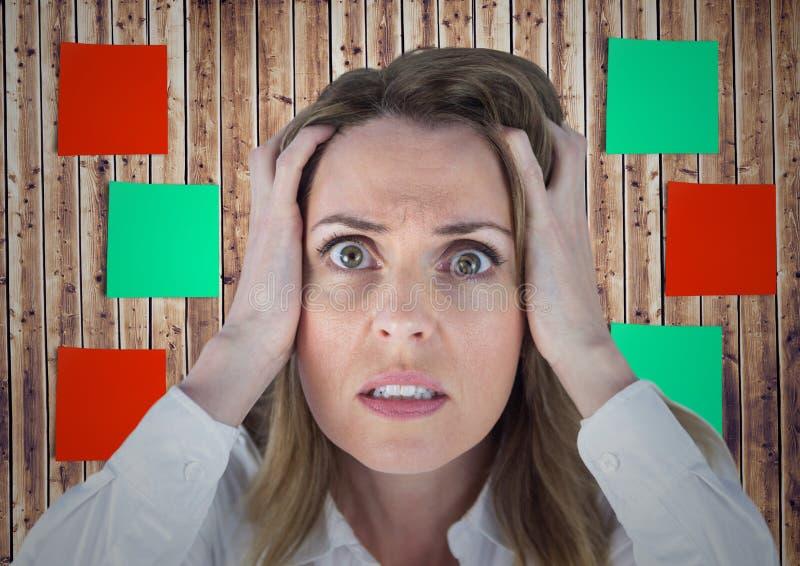 Femme frustrante avec des mains sur son visage contre la note collante sur le fond en bois images stock