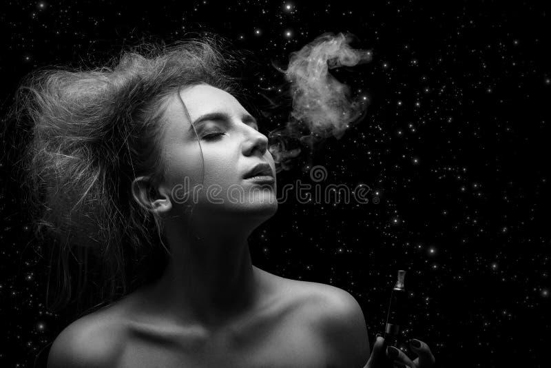Femme fumant la cigarette électronique photo libre de droits