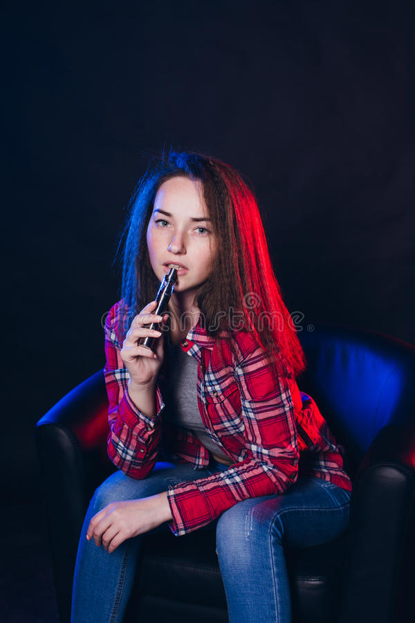 Femme fumant la cigarette électronique avec de la fumée photos libres de droits