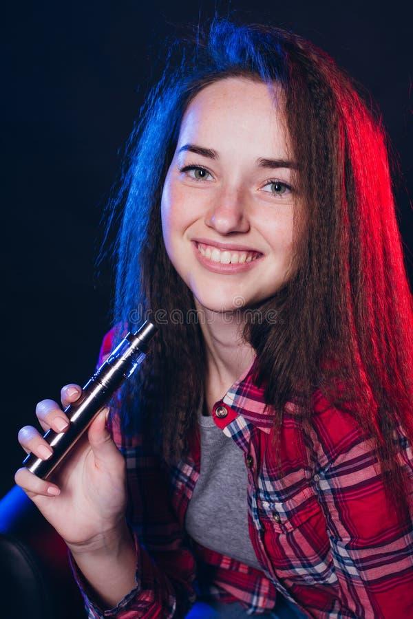 Femme fumant la cigarette électronique avec de la fumée photo stock
