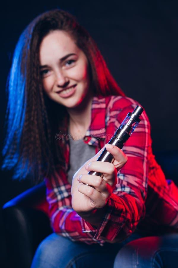 Femme fumant la cigarette électronique avec de la fumée image libre de droits