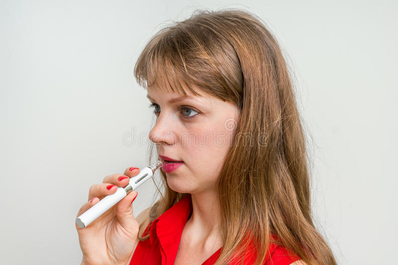 Femme fumant une cigarette électronique photo stock
