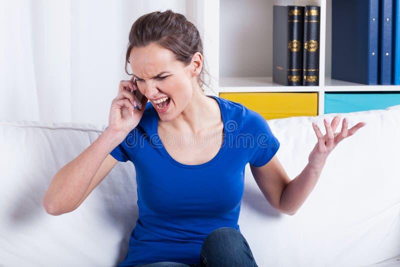 Femme furieuse parlant à un téléphone photo libre de droits