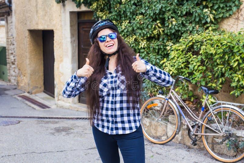 Femme gaie au casque et lunettes de soleil, chemise montrant des pouces sur la bicyclette et la rue de fond images stock
