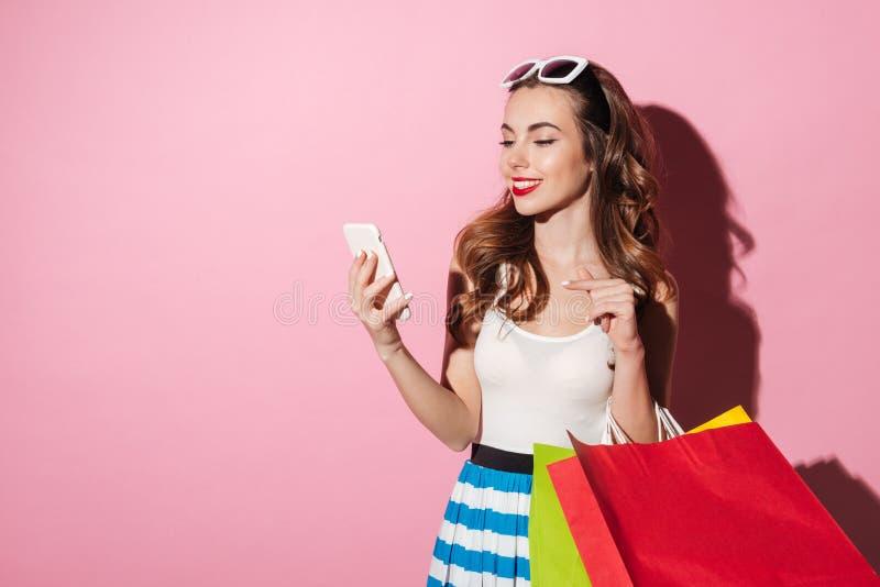 Femme gaie avec des paniers introduisant le message au téléphone portable images libres de droits