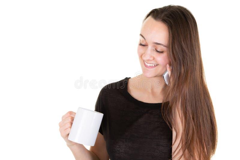 Femme gaie avec la longs tasse et téléphone portable de café bruns de tasse de participation de cheveux dans des mains tout en re photographie stock