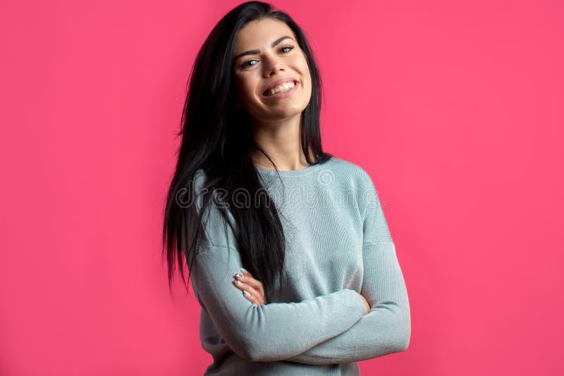 Femme gaie avec les bras croisés d'isolement sur le fond rose image libre de droits