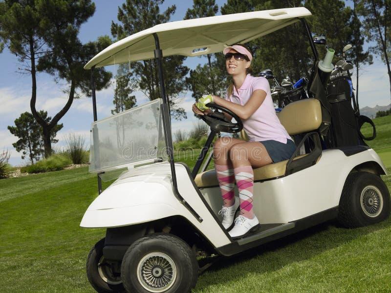 Femme gaie conduisant le chariot de golf photos libres de droits