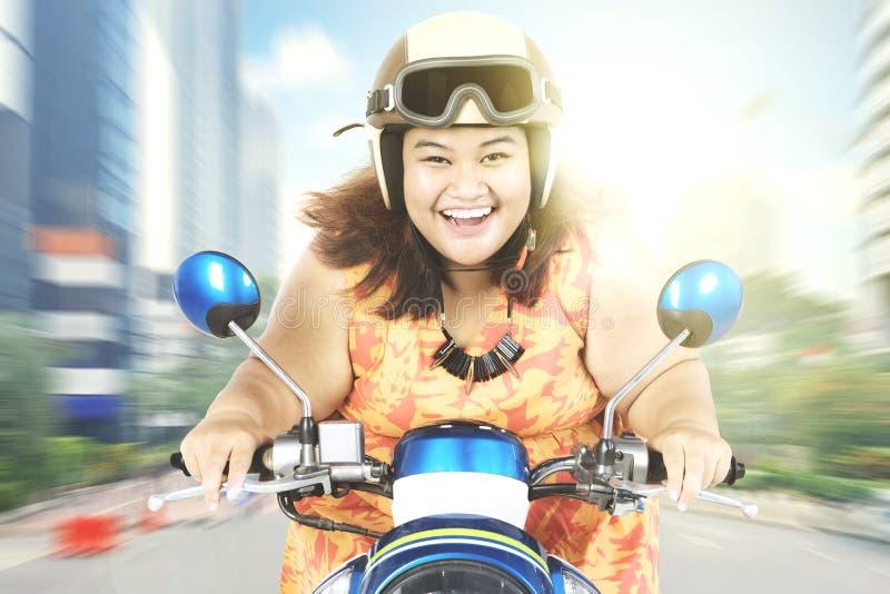 Femme gaie conduisant une moto photo libre de droits