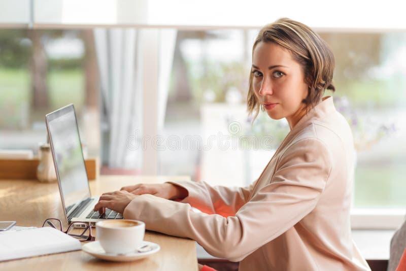 Femme gaie d'affaires dans le café dactylographiant sur l'ordinateur portable avec du café photos stock