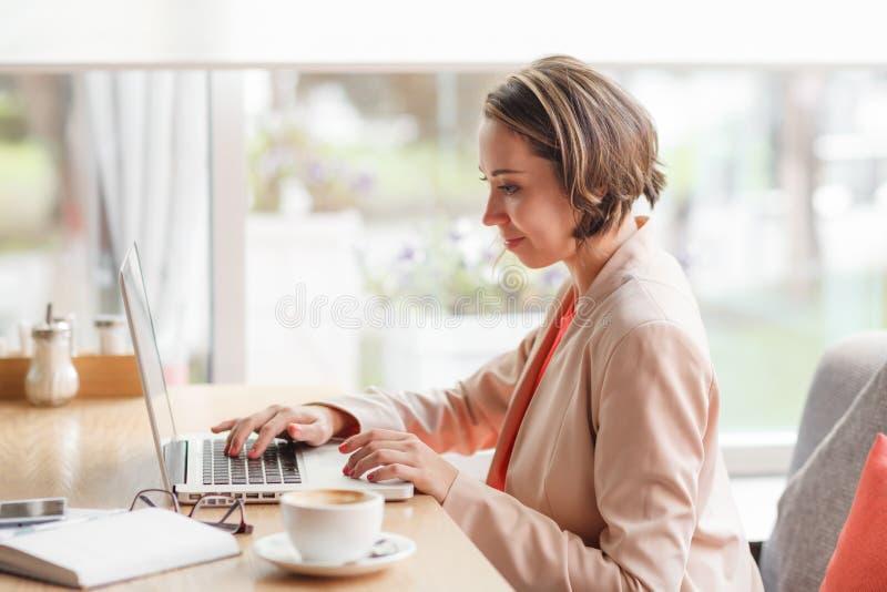 Femme gaie d'affaires dans le café dactylographiant sur l'ordinateur portable avec du café images libres de droits