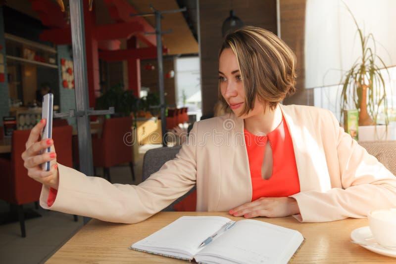 Femme gaie d'affaires dans le café prenant le selfie par phone mobile images libres de droits