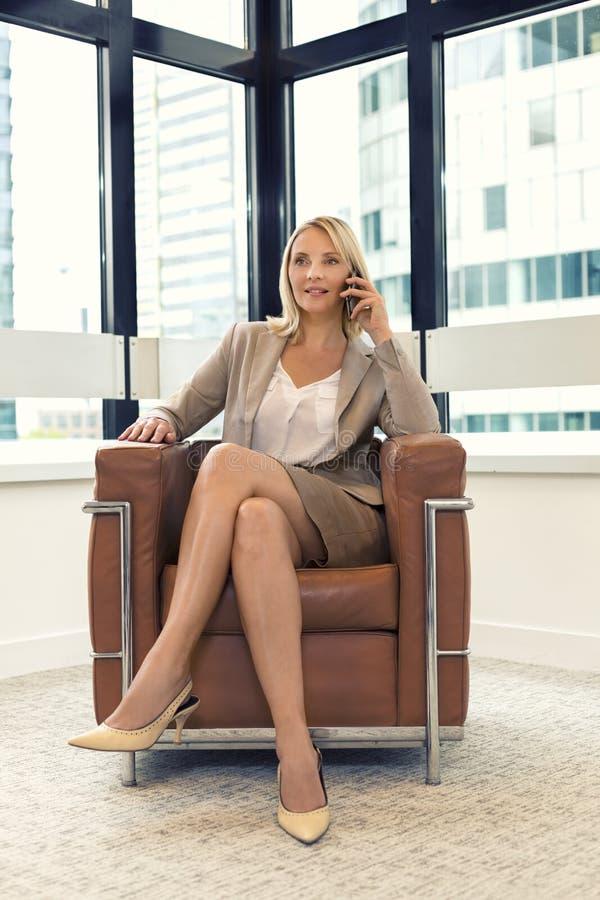 Femme gaie d'affaires s'asseyant dans une chaise au téléphone portable photo stock