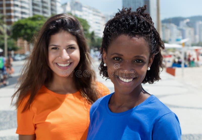Femme gaie d'afro-américain avec l'amie caucasienne photo libre de droits