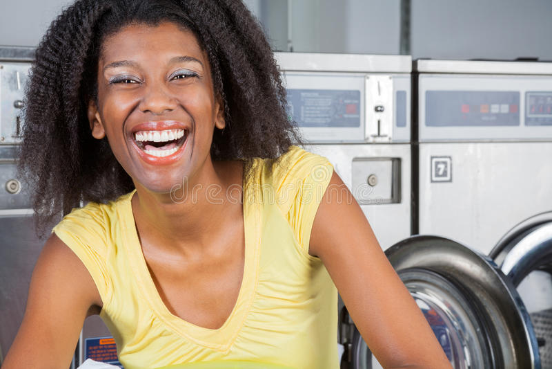 Femme gaie dans la blanchisserie photo stock