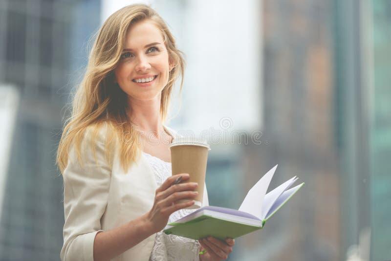 Femme gaie dans le café potable de rue image stock