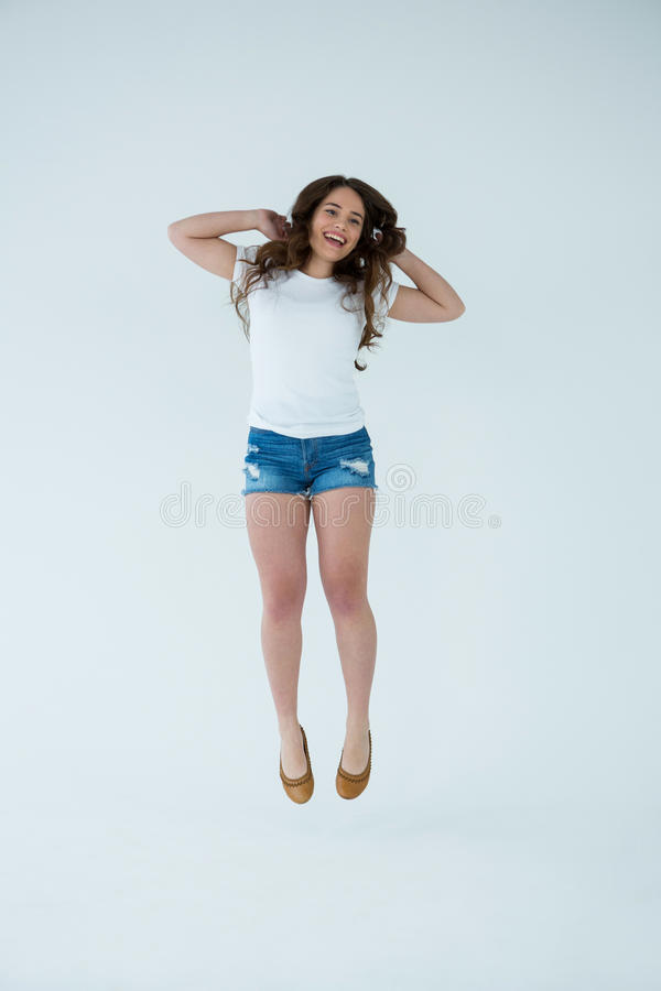 Femme gaie dans sauter de T-shirt blanc et de pantalon chaud photos stock