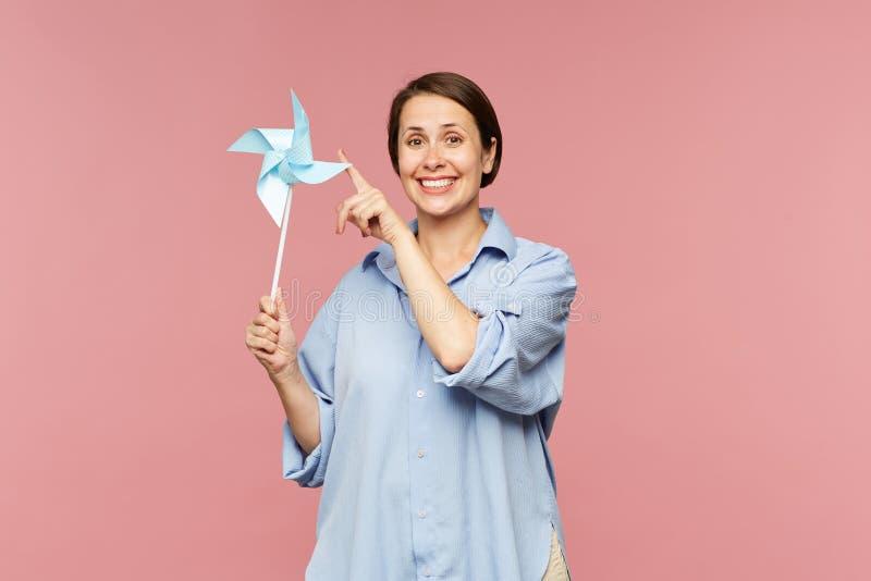 Femme gaie de brune dans la chemise bleue jouant avec la toupie de papier photos libres de droits