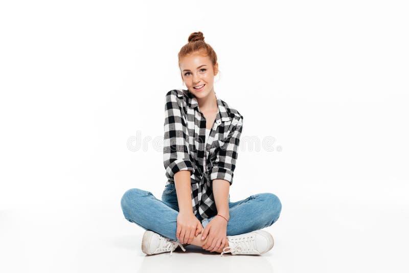 Femme gaie de gingembre dans la chemise et des jeans se reposant sur le plancher image stock