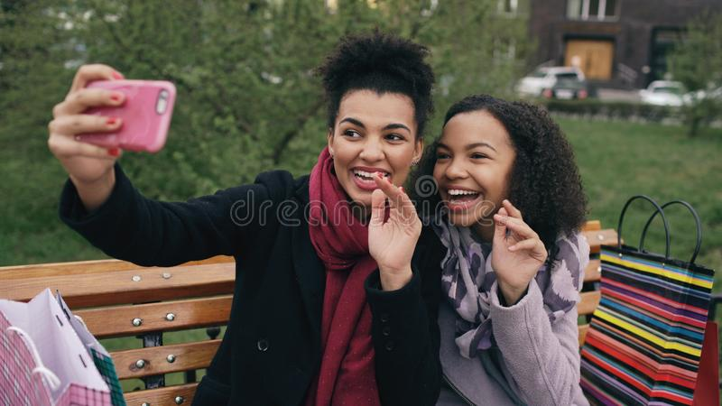 Femme gaie du métis deux avec des paniers parlant à l'appel visuel avec le smartpone Les jeunes filles s'asseyant sur le banc ont photos libres de droits