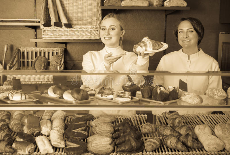 Femme gaie et jeune fille proposant la pâtisserie photo stock