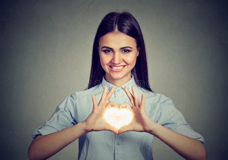 Femme gaie faisant le signe de coeur avec des mains images libres de droits