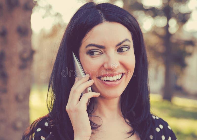 Femme gaie parlant d'un téléphone dehors photographie stock libre de droits
