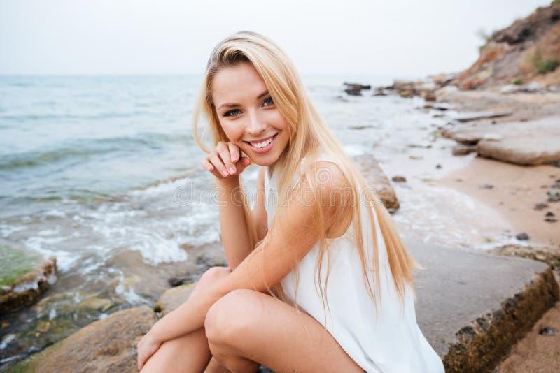 Femme gaie s'asseyant sur les roches près de la mer photographie stock